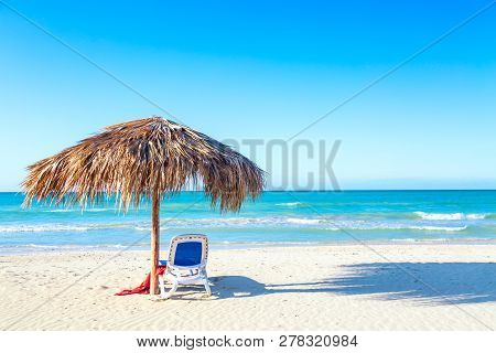 A Sun Lounger Under An Umbrella On The Sandy Beach By The Sea And Sky. Vacation Background. Idyllic