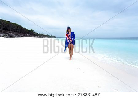 Woman Standing On Idyllic Beach With Australian Flag Sarong Draped Around Her,   She Is Also Wearing