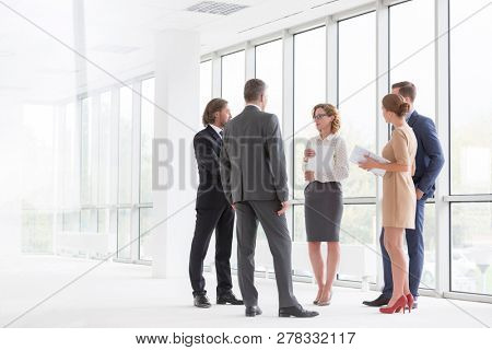 Business colleagues discussing while standing against window in new office