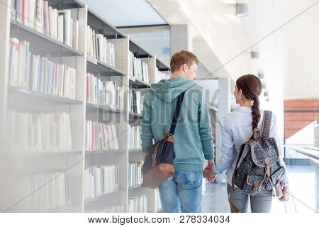 Rear view of couple walking while holding hands in library