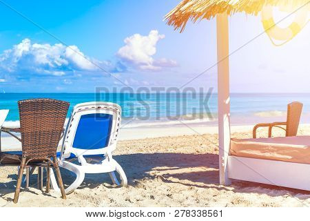 Sun Lounger Near Straw Umbrella Bed On The Sandy Beach By The Sea And Sky. Vacation Background. Idyl