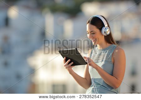Happy Woman Litening To Music Browsing Tablet Content In A Town At Sunset