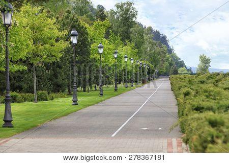 A Straight Asphalt Road And A Bike Path Go Along A Beautiful, Clipped Green Lawn Through A Summer Pa