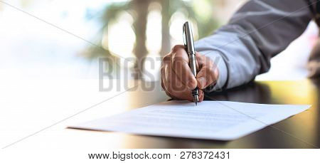 Businessman Signing An Official Document In Office