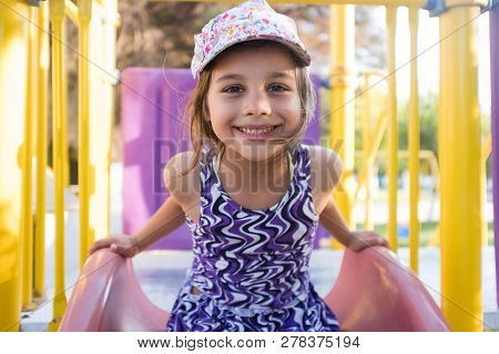 Little Child Girl Playing At Playground Outdoors In Summer
