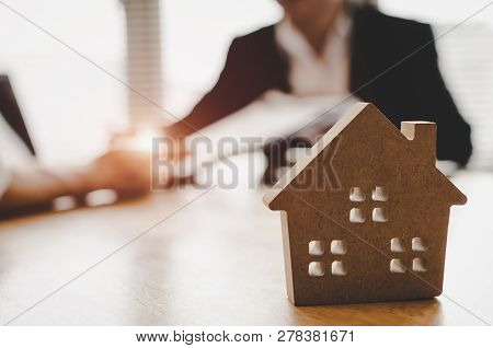 Customer Signing Contract For Buying House With Real Estate Broker In Estate Agent Office Behind Woo