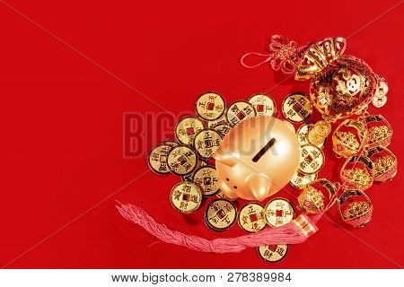 Piggy Bank Standing On Golden Coin And Red Envelopes With Chinese Ornament Over Red Background. Chin