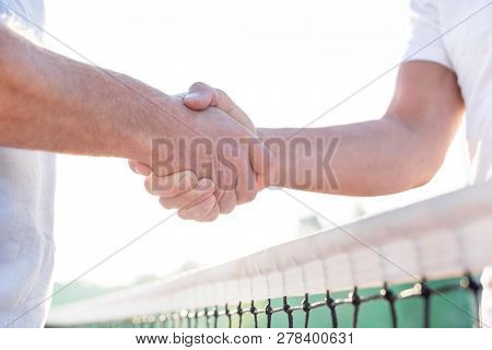 Midsection of men shaking hands while standing at tennis court against clear sky