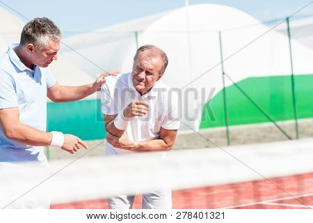 Mature man helping senior friend with elbow injury while playing tennis on sunny day