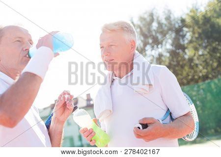 Mature man looking senior friend drinking from bottle while standing on tennis court during summer