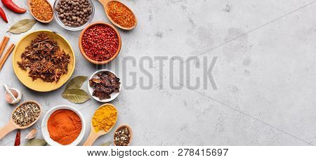 Dried Spices And Seasonings In Bowls On Grey Background, Copy Space, Top View