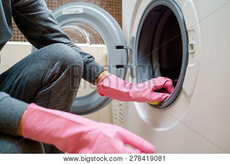 Image of woman 's hand in pink rubber glove washing washing machine