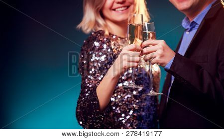 Photo of woman in brilliant dress and men with wine glasses with champagne on blue background