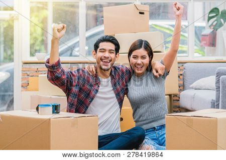 Asian Young Couple Are Glad After Successfull Packing The Big Cardboard Box For Moving In New House,