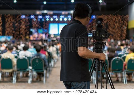 Rear Side Of Video Cameraman Taking Photograph To Abstract Blurred Photo Of Conference Hall Or Semin