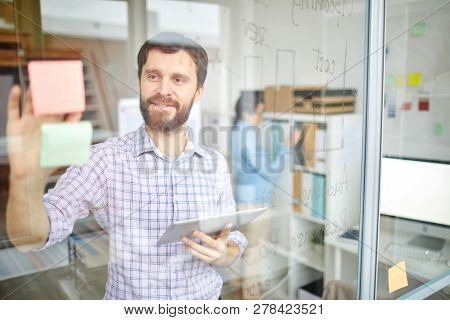Young bearded manager with gadget reading notepapers on transparent board while browsing in the net