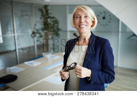 Mature businesswoman with toothy smile and blond hair standing in front of camera in boardroom