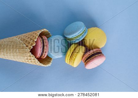 Ice Cream Waffle Cone With Colorful Macaron Or Macaroon On Blue Pastel Background Top View. Colorful