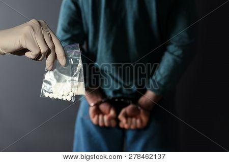 Police Worker Holding Drugs In Plastic Bags Near Arrested Dealer On Color Background