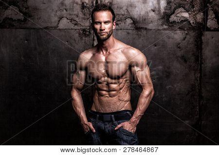 Studio Shot Of Strong Athletic Man On Dark Grunge Background