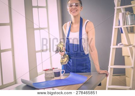 Worker woman with drill standing in new home