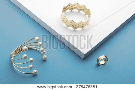 Golden Bracelets And Golden Ring On White And Blue Background - Zigzag Bracelet And Pearl Golden Bra