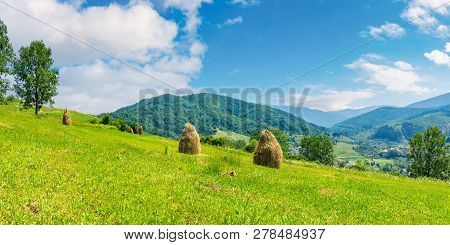 Haystacks On A Grassy Hill In Summer. Beautiful Summer Landscape In Mountains. Carpathian Countrysid