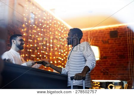 Young African-american traveler consulting with hotel receptionist by counter during accommodation