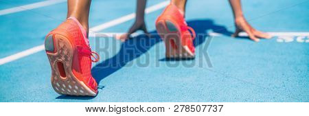 Sprinter waiting for start of race on running tracks at outdoor stadium. Sport and fitness runner woman athlete on blue run track with orange running shoes. Panorama banner.