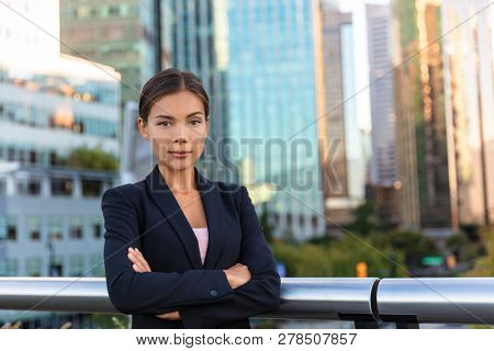 Asian businesswoman. Serious business woman portrait. Chinese professional in black suit in city background, downtown people lifestyle. Confident lady with crossed arms.