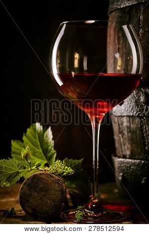 Red Wine In A Glass With Vine Leaves And Cork