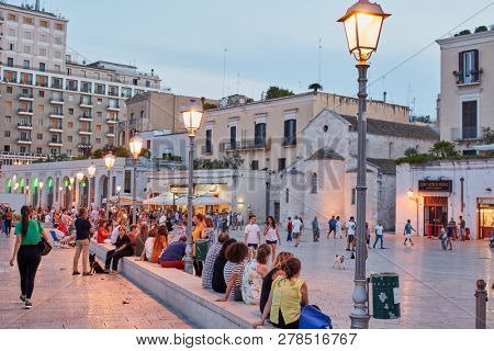 BARI, ITALY - AUGUST 17, 2018: People resting on Piazza Ferrarese in a summer evening. The square is filled with very busy bars and restaurants and has become a must for those enjoying Bari nightlife