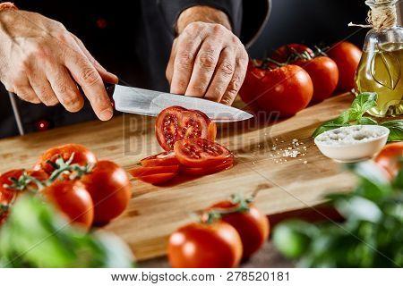 Chef Slicing Fresh Tomato For A Salad