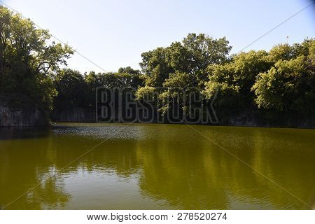 Henry C. Palmisano Nature Park with water lake in a former stone quarry in summer surrounded by lush green trees poster