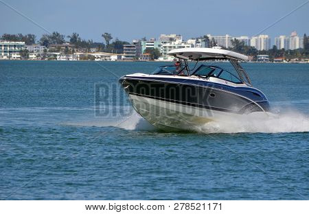 High-end Dark Blue Motor Boat With White Trim Speeding On The Florida Intra-coastal Waterway Off Mia