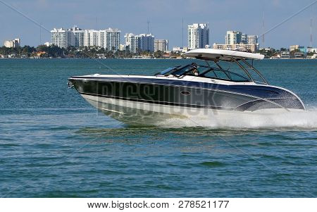 Motorboat speeding on the Florida Intra-Coastal Waterway with Miami condo skyline in the background. poster