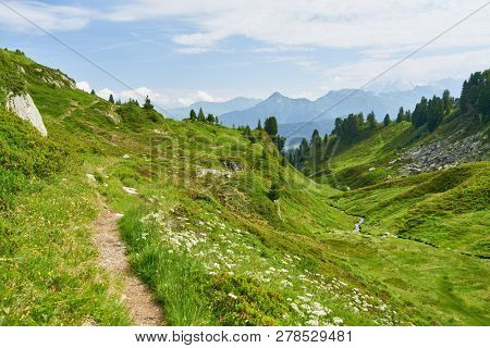 Hiking trail in the mountains beside valley with brook in the French Alps