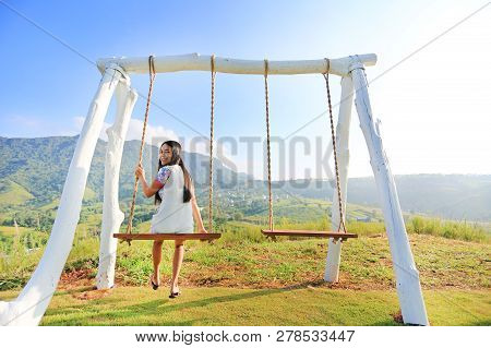 Smiling Young Woman Relaxing By Swing On Hillside At Morning Sunrise.