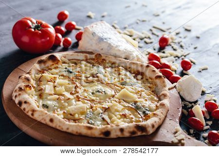 Four cheese pizza on wooden board. Tomatoes, blue cheese, parmesan and mozzarella in the background. Popular traditional food.