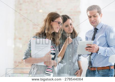 Creative businessman using digital tablet with colleagues in office