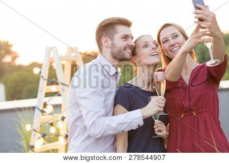 Portrait of smiling mature business colleagues standing with wineglasses at party on rooftop