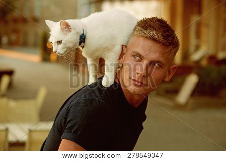 Curious explorer. Happy man on walk with cat pet. Muscular man hold cute pedigree cat. Happy cat owner with muscular look. Cat stands on back of his owner. poster
