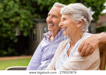 Senior couple sitting together on bench at park. Elderly married couple sitting outdoor and relaxing. Romantic husband embrace his wife while looking away and smiling. Future and retirement concept.