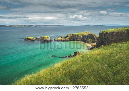 Irish bay with turquoise water and grass covered land. Northern Ireland. Breathtaking marine landscape. Grass covered land of the stunning shoreline. Beauty of wild untouched nature.