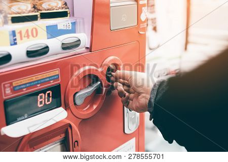 Woman Hand Inserting Coin In Vending Machine At Street Public.