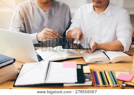 Two Students Studying And Learning In Library With A Laptop And Notes.