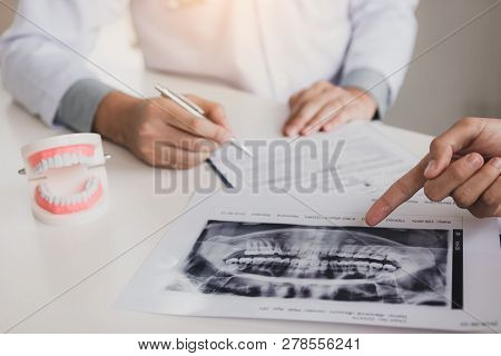 Dentist Hand Holding Pen And Talking To The Patient With Pointing X-ray Picture About Medication And