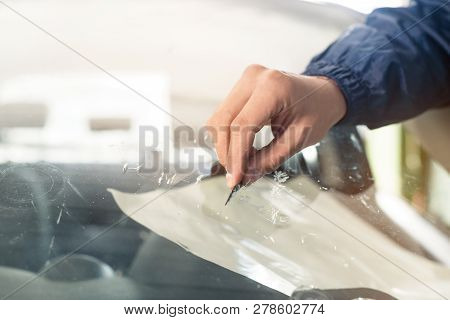 Close Up Automobile Glazier Worker Fixing And Repair Windscreen Or Windshield Of A Car In Auto Servi