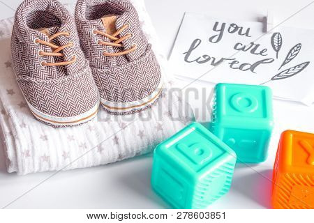 Babys Bootees And Gift Box On Wooden Background