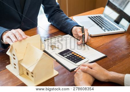 Businessman Signs Contract Behind Home Architectural Model Discussion With A Real Estate Agent Renta